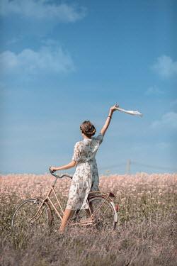 Ildiko Neer Timeless woman waving on bike with handkerchief