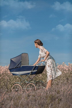 Ildiko Neer Young woman with pram in meadow