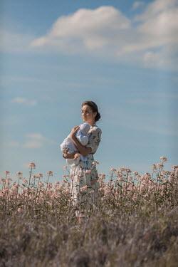 Ildiko Neer Timeless woman holding baby in meadow
