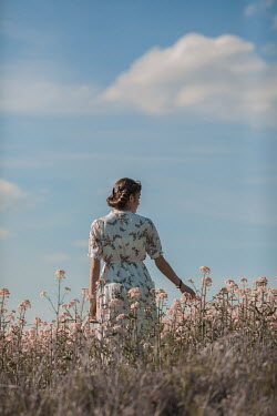 Ildiko Neer Timeless woman standing in meadow