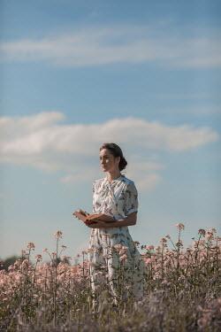 Ildiko Neer Timeless woman holding book in meadow