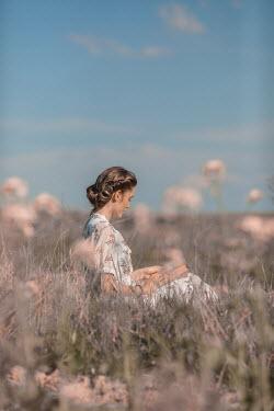 Ildiko Neer Young woman reading in grass