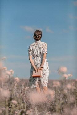 Ildiko Neer Young woman holding book in meadow