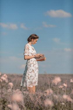 Ildiko Neer Young woman reading book in meadow