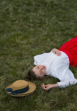 Joanna Czogala HISTORICAL WOMAN WITH HAT LYING ON GRASS