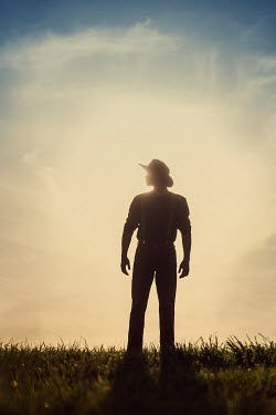 Magdalena Russocka historical man wearing hat standing in field at sunset