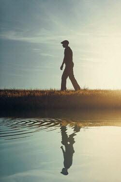 Magdalena Russocka retro man walking by river at sunset