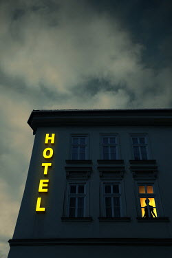 Magdalena Russocka silhouette of woman in illuminated window of old hotel at night