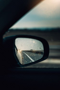 Magdalena Russocka car with headlights on highway reflected in car wing mirror