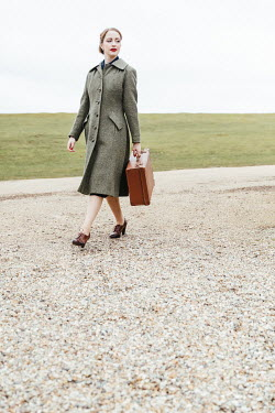 Matilda Delves 1940S WOMAN CARRYING SUITCASE ON COUNTRY ROAD