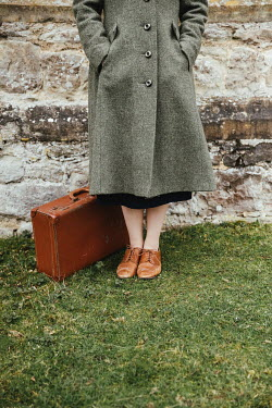 Matilda Delves RETRO WOMAN WITH SUITCASE STANDING OUTDOORS