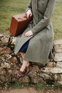 Matilda Delves RETRO WOMAN WITH SUITCASE SITTING ON WALL OUTDOORS