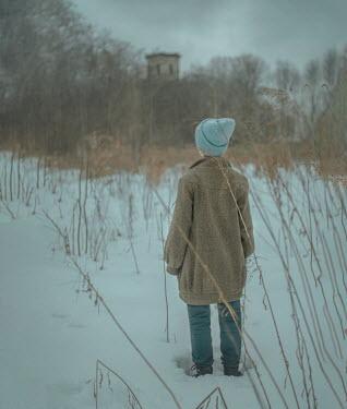 Svitozar Bilorusov GIRL STANDING IN SNOWY FIELD WATCHING BUILDING