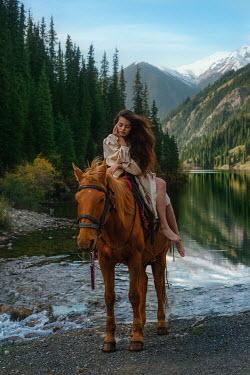 Tatiana Mertsalova BRUNETTE WOMAN ON HORSE BY RIVER AND MOUNTAINS