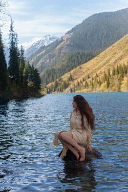 Tatiana Mertsalova WOMAN SITTING ON ROCK IN RIVER WITH MOUNTAINS