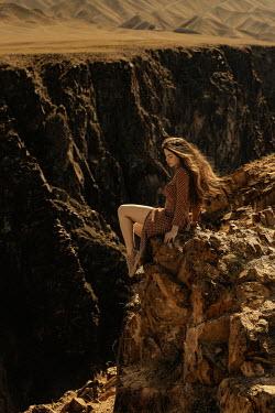 Tatiana Mertsalova WOMAN WITH LONG DARK HAIR ON CLIFF IN DESERT