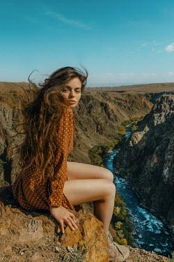 Tatiana Mertsalova WOMAN WITH LONG DARK HAIR ON CLIFF BY RIVER