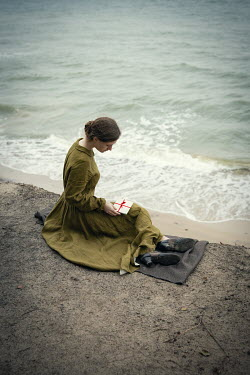 Natasza Fiedotjew vintage woman with letter sitting on cliff above seashore