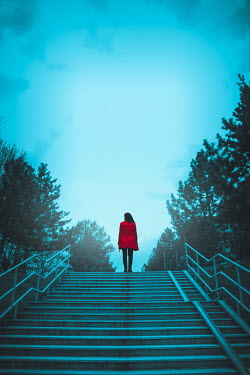 Joanna Czogala WOMAN IN RED COAT ON STEPS AT DUSK