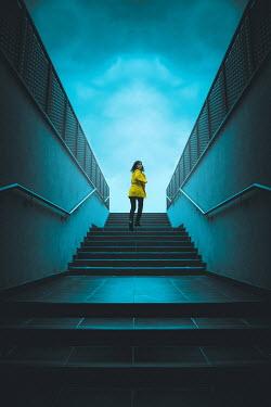 Joanna Czogala SCARED WOMAN RUNNING ON URBAN STEPS