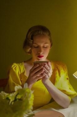 Svitozar Bilorusov RETRO WOMAN SITTING INDOORS DRINKING COFFEE