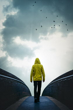 Natasza Fiedotjew man in yellow jacket walking on bridge