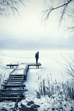 Natasza Fiedotjew man in black coat and fedora hat standing on jetty in winter