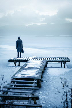 Natasza Fiedotjew man with briefcase in black coat and fedora hat standing on jetty in winter