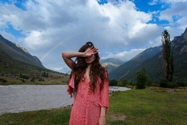 Tatiana Mertsalova BRUNETTE WOMAN COVERING FACE STANDING BY LAKE