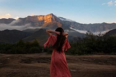 Tatiana Mertsalova BRUNETTE WOMAN STANDING WATCHING MISTY MOUNTAINS
