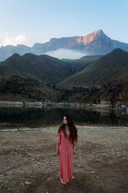 Tatiana Mertsalova BRUNETTE WOMAN STANDING BY LAKE WITH MOUNTAINS