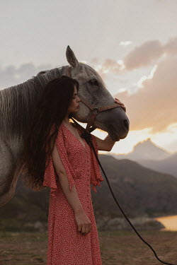 Tatiana Mertsalova BRUNETTE WOMAN WITH HORSE BY LAKE AT DUSK
