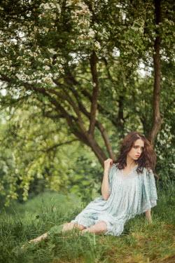 Klaudia Rataj BRUNETTE WOMAN SITTING BY TREE IN BLOSSOM