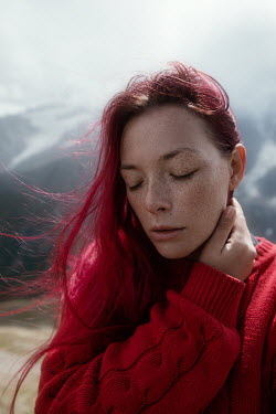 Tatiana Mertsalova WOMAN WITH RED HAIR AND RED SWEATER BY MOUNTAIN