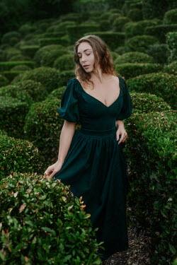 Tatiana Mertsalova WOMAN IN GREEN DRESS IN GARDEN WITH HEDGES