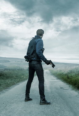 CollaborationJS MAN WITH GUN STANDING ON COUNTRY ROAD