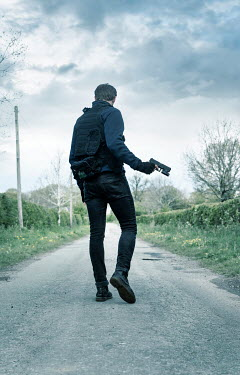 CollaborationJS MAN WITH GUN WALKING ON COUNTRY ROAD
