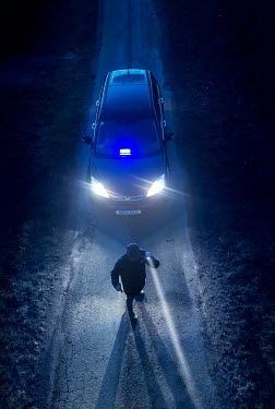 CollaborationJS DETECTIVE WITH TORCH AND CAR ON ROAD AT NIGHT
