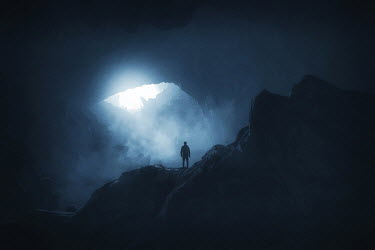Andrei Cosma SILHOUETTED MAN STANDING IN LARGE CAVE