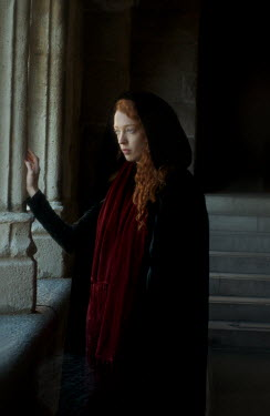 Daniel Murtagh WOMAN WITH RED HAIR AND CAPE INSIDE BUILDING