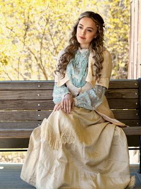 Elisabeth Ansley BLONDE WOMAN SITTING ON BENCH ON VERANDA