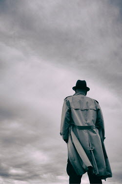 Tim Robinson MAN IN HAT AND RAINCOAT WITH CLOUDY SKY