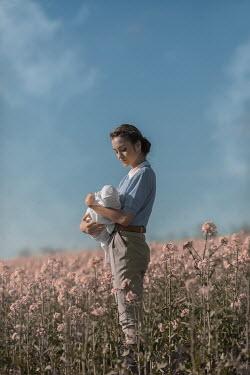 Ildiko Neer Vintage woman holding baby in meadow
