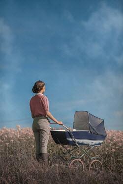 Ildiko Neer Land girl with pram in meadow