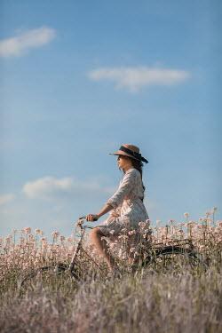 Ildiko Neer Young woman on bicycle in meadow