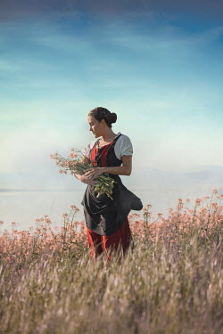 Ildiko Neer Historical woman holding flower bouquet in meadow