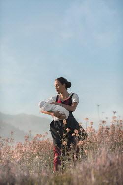 Ildiko Neer Historical woman holding baby in meadow