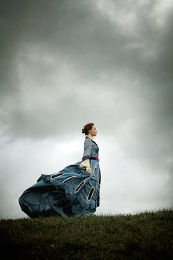 Miguel Sobreira HISTORICAL WOMAN STANDING IN WINDY FIELD