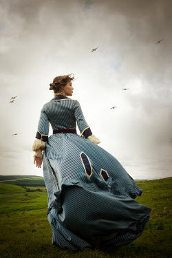 Miguel Sobreira HISTORICAL WOMAN STANDING IN WINDY LANDSCAPE