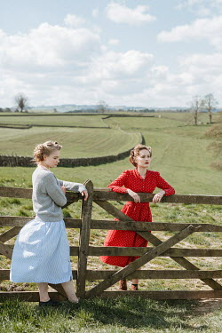 Shelley Richmond TOW RETRO WOMEN STANDING BY GATE IN COUNTRYSIDE